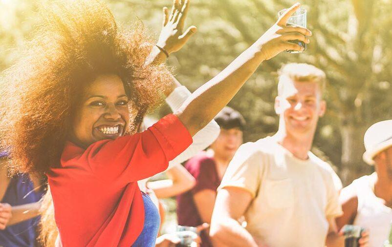 mulher negra feliz dançando em festa econômica