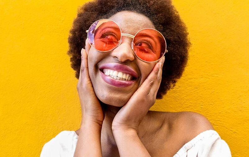 Mulher negra com óculos laranja sorrindo com uma parede amarela ao fundo