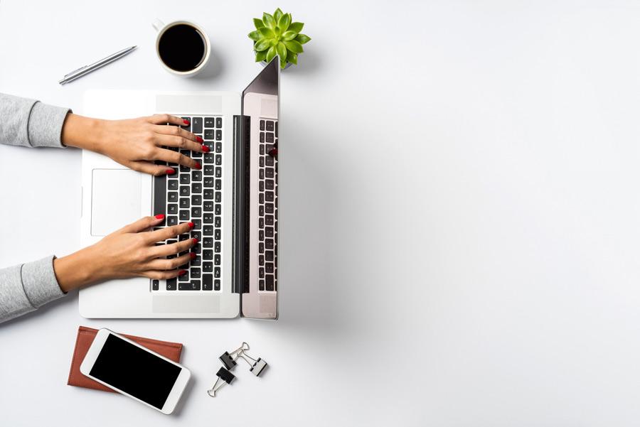 Imagem de pessoa mexendo no notebook, com celular ao lado direito e xícara de café e caneta do lado esquerdo