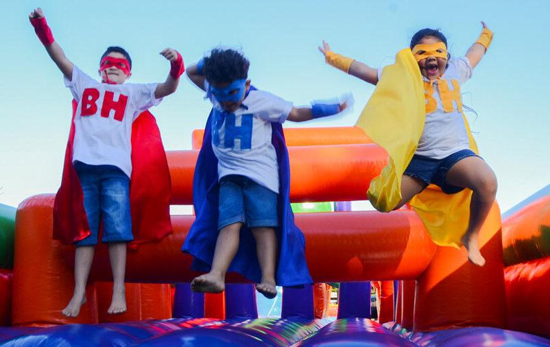 crianças pulando em brinquedo inflável no dia das crianças