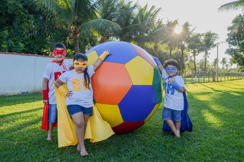 Crianças vestidas de super-herói apoiadas em bola inflável