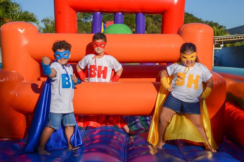 crianças vestidas de super-heróis em brinquedo inflável