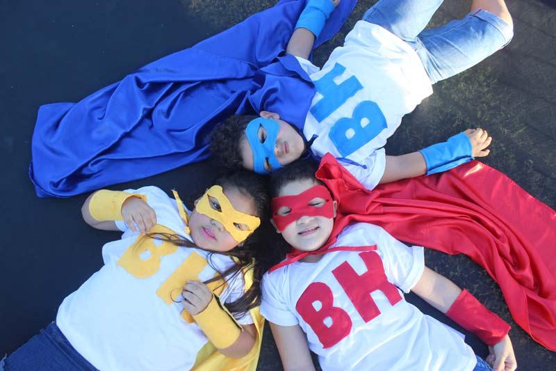 crianças deitadas no gramado vestidas de super-heróis