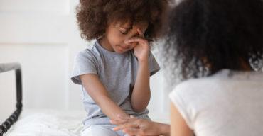 Menina negra diagnosticada com ansiedade infantil chorando