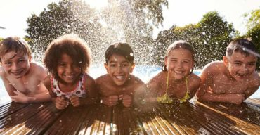 Crianças unidas na borda da piscina para mostrar que é possível aprender brincando
