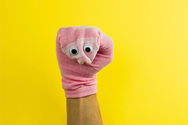 Fantoche formado por uma meia rosa em uma mão masculina com fundo amarelo
