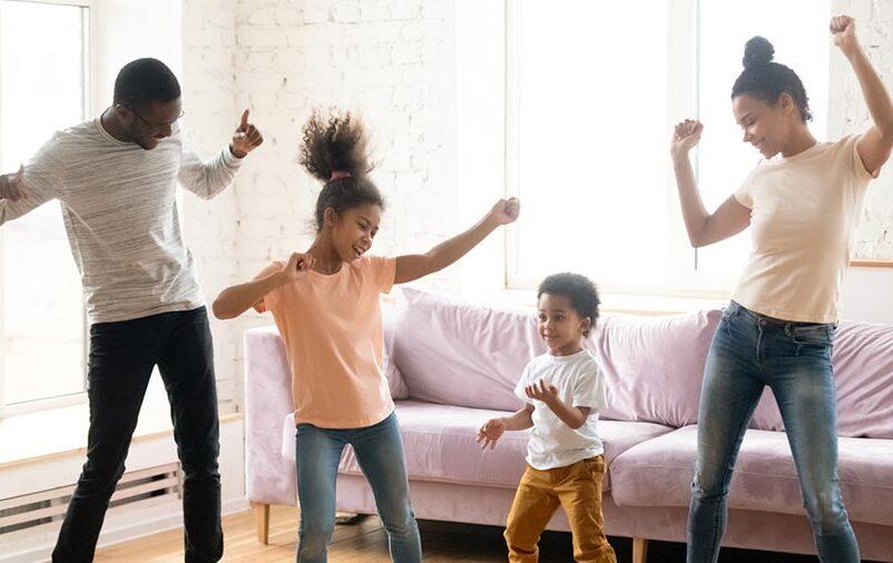 Pais e filhos dançando e mostrando uma das formas de como estimular a diversão em casa