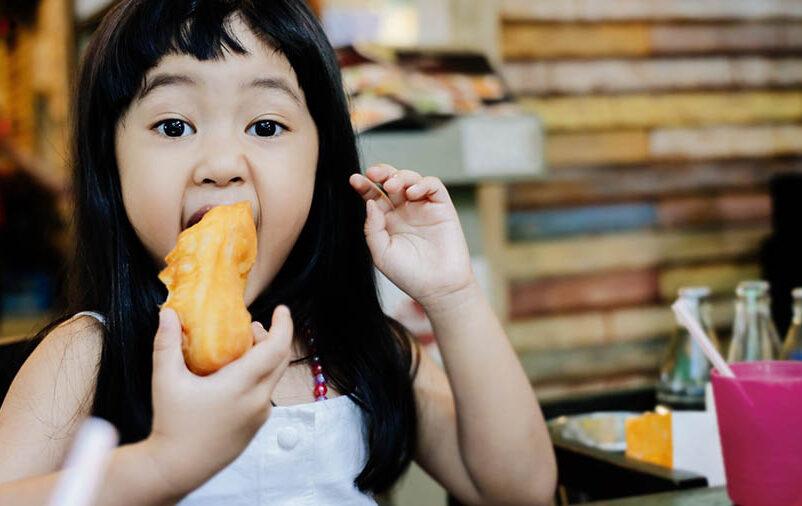 Vemos uma criança comendo. Veja como montar um espaço kids em restaurantes!