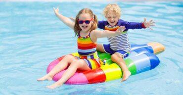 Na imagem vemos crianças se divertindo no salão de festa com piscina.
