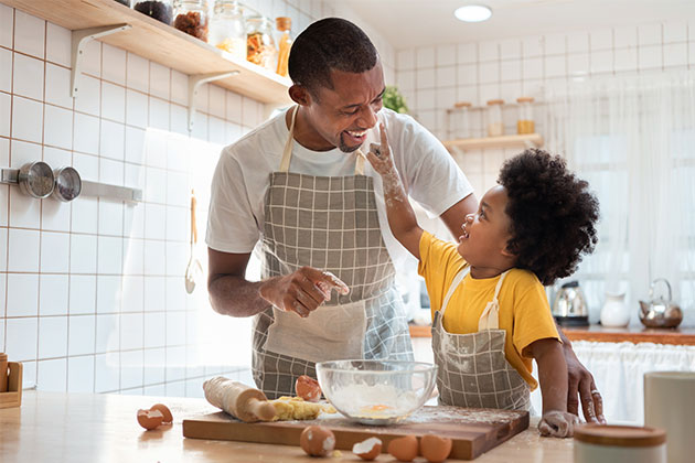 pai e filho cozinhando juntos como forma de comemoração do Dia das Crianças