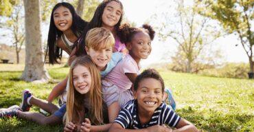 imagem de 5 crianças deitadas ao ar livre